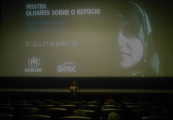 O refugiado Abdulbaset Jarour apresenta a programação de abertura da mostra Olhares sobre Refúgio (Foto: Géssica Brandino)